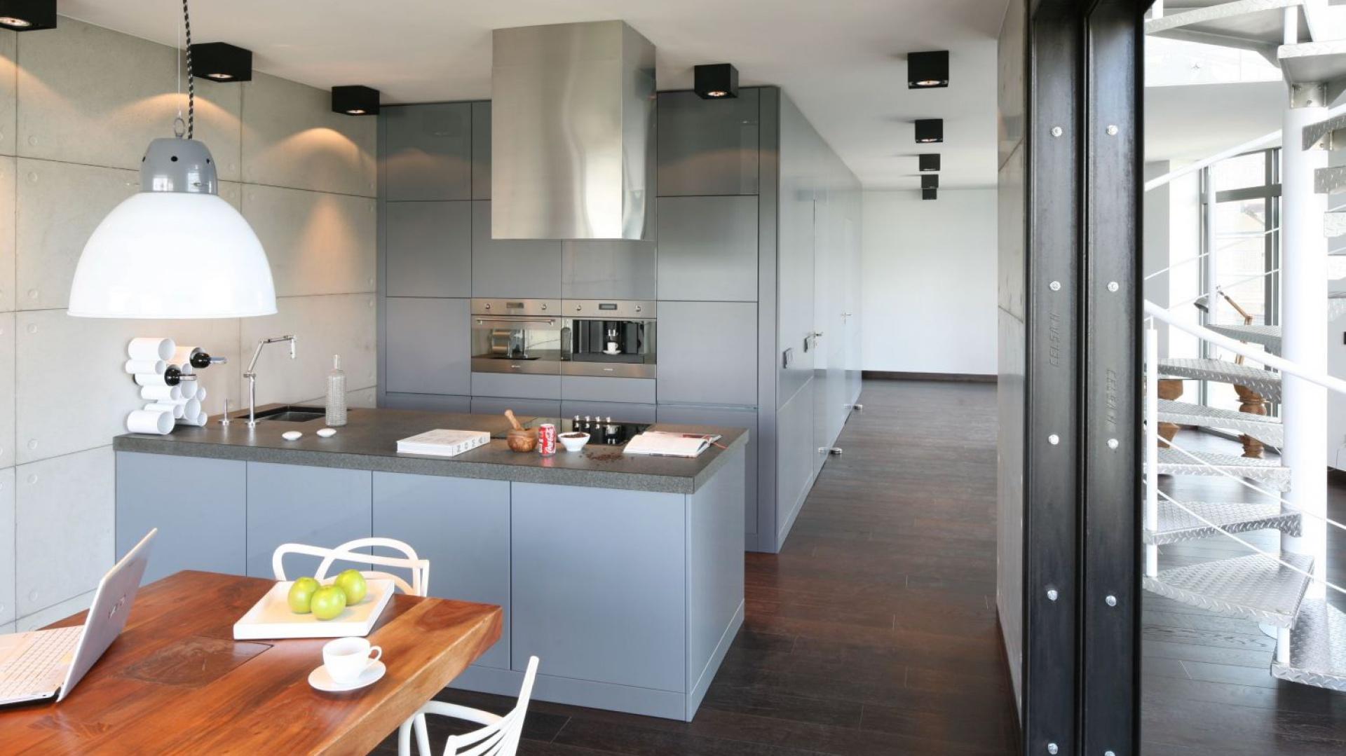Aranżację kuchni utrzymano w stylu soft loft. Szare, minimalistyczne, nowoczesne meble idealnie współgrają z betonem na ścianie. Projekt: Justyna Smolec. Fot. Bartosz Jarosz.