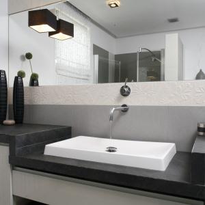 Duża tafla lustra dodaje przestrzeni wąskiej łazience w szarościach. Projekt: Małgorzata Mazur. Fot. Bartosz Jarosz.