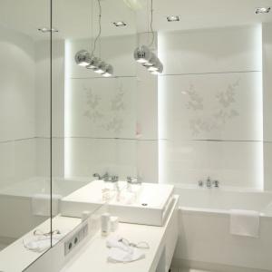 Biała łazienka zyskuje głębię dzięki wielkiej tafli lustra zamontowanej na ścianie. Projekt: Anna Maria Sokołowska. Fot. Bartosz Jarosz.