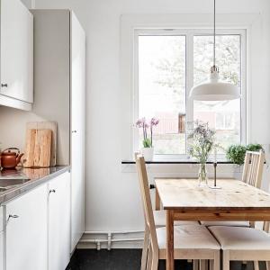 Biała kuchnia została wizualnie ocieplona obecnością drewnianego stołu jadalnianego. W jadalni posiłek mogą zjeść cztery osoby. Fot. Stadshem/Janne Olander.