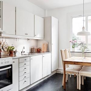 W małym mieszkaniu udało się wygospodarować miejsce na sporych rozmiarów kuchnię. Za sprawą białej zabudowy oraz braku firanek w oknach, kuchnia wydaje się bardzo przestronna. Fot. Stadshem/Janne Olander.