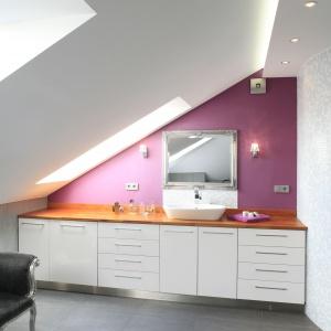 Łazienka pod skosami ma szarą podłogę oraz ścianę w intensywnym kobiecym kolorze. Projekt: Dominika Grabowska. Fot. Bartosz Jarosz.