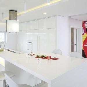 Minimalistyczna, biała kuchnia z wysoką zabudową pozbawiona jest jakichkolwiek dolnych szafek. Dlatego też, wyspa kuchenna jest duża i pełni kilka funkcji jednocześnie. Projekt: Dominik Respondek. Fot. Bartosz Jarosz.
