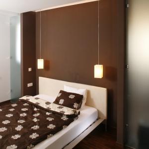 Nic tak nie podkreśla przytulności wnętrza jak nastrojowe oświetlenie. Wiszące lampki nocne pięknie podkreślają wykończenie ściany nad łóżkiem. Projekt: Piotr Gierałtowski. Fot. Bartosz Jarosz.