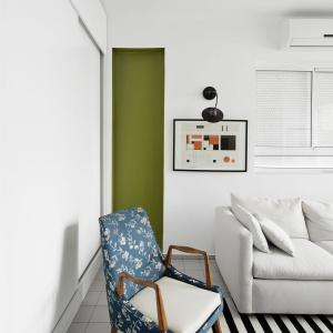 Charakter strefie dziennej dodają nietuzinkowe elementy, jak czarno-biały dywan oraz stylowy fotel z kwiecistą tapicerką. Projekt: Studio Raanan Stern. Fot. Gidon Levin.
