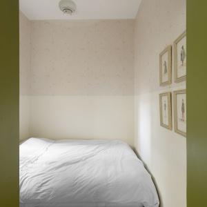 W sypialni postawiono na stonowaną, ciepłą kolorystykę - wariacje na temat różów i beżów. Ciekawym akcentem jest ściana w dwóch wykończeniach - na górze zdobi ją wzorzysta tapeta, na dole - farba. Projekt: Studio Raanan Stern. Fot. Gidon Levin.
