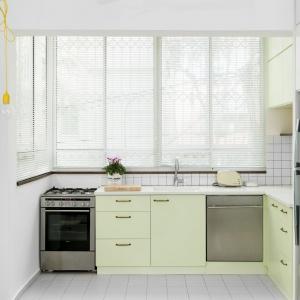 Zabudowa kuchenna w jasnożółtym, wyblakłym kolorze nawiązuje do kolorystyki żółtego oplotu, na którym zawisła odsłonięta żarówka. Projekt: Studio Raanan Stern. Fot. Gidon Levin.