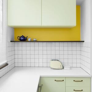 Choć w mieszkaniu króluje biel, nie brak również akcentów w innym kolorze. W kuchni jest to jasna, blada zieleń zabudowy oraz żółty na ścianie nad blatem. Projekt: Studio Raanan Stern. Fot. Gidon Levin.