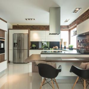 Nowoczesna kuchnia, w której przeważa biel i połyskujące powierzchnie - zarówno w formie zabudowy kuchennej jak i jednorodnej posadzki. Cegła na ścianie swoją chropowatą, matową fakturą efektownie przełamuje dominację połysku. Fot. Max Kuchnie/Pracownia Mebli Vigo.