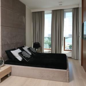 Ściana naprzeciw łóżka wykończona drewnem to wyrazisty element wnętrza. Zawieszony na niej telewizor, jest pięknie wyeksponowany. Projekt: Anna Maria Sokołowska. Fot. Bartosz Jarosz.
