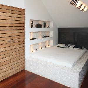 Mała sypialnia na poddaszu została urządzona spójnie i funkcjonalnie. Łóżko na podeście, szafa o ciekawym wzorze oraz ściana wykończona drewnem dopełniają wnętrze. Projekt: Katarzyna Mikulska-Sękalska. Fot. Bartosz Jarosz.