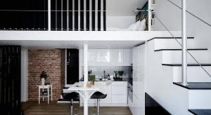 Małe mieszkanie z antresolą zostało urządzone w bieli i czerni, ożywionej cegłą na ścianie. Zobaczcie, jak modnie urządzić 35 metrów.
