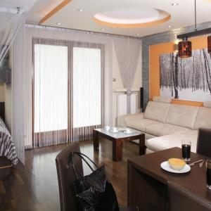 W malutkim apartamencie wypoczynkowym salon został połączony nie tylko z kuchnią, ale nawet sypialnią. Organizuje go narożna sofa w jasnym kolorze. Projekt: Jolanta Kwilman. Fot. Bartosz Jarosz.