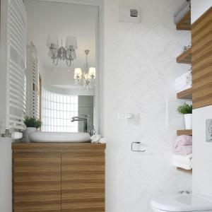 Szafka podumywalkowa oraz dekoracyjne akcenty z drewna świetnie ocieplają łazienkę. Projekt: Małgorzata Mazur. Fot. Bartosz Jarosz.