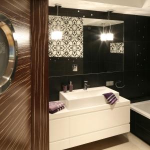 Do łazienki prowadzą drzwi w okleinie z drewnianym motywem. Dodatkową dekoracją jest okrągłe przeszklenie, nawiązujące do okien w kajutach marynarskich. Projekt: Małgorzata Galewska. Fot. Bartosz Jarosz.