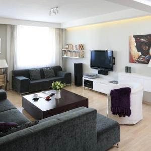 W przestronnym, eleganckim salonie z jasną, drewnianą podłogą i białymi ścianami kontrastują tapicerowane, antracytowe meble wypoczynkowe. Projekt: Małgorzata Galewska. Fot. Bartosz Jarosz.