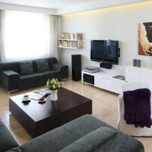 Przestronny salon to miejsce, w którym wszyscy domownicy mogą usiąść na miękkich meblach wypoczynkowych i zrelaksować się przed TV. Projekt: Małgorzata Galewska. Fot. Bartosz Jarosz.