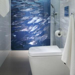 Niebieska fototapeta z nadrukiem morskich rybek dodaje wąskiej łazience głębi. Projekt: Anna Maria Sokołowska. Fot. Bartosz Jarosz.