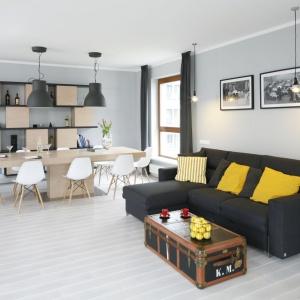Przestrzeń salonu to królestwo oszczędnej elegancji. Zamiast dywanów mamy tu naturalną deskę dębową, a obszerny zestaw wypoczynkowy zastąpił elegancki narożnik. Projekt: Maciejka Peszyńska-Drwes. Fot. Bartosz Jarosz.