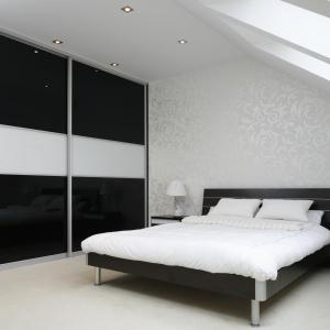 Sypialnia urządzona w czerni i bieli. Połyskująca tapeta za łóżkiem jest wyrazem kobiecej elegancji, zaś głębi wnętrzu dodaje głęboka czerń wokół. Projekt: Magdalena Wielgus-Biały. Fot. Bartosz Jarosz.