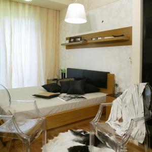 Sypialnia w stylu zainspirowanym naturą. Jasne ściany, drewno i skóra na podłodze. Aby nie było w niej nudo, projektantka postawiła na kontrast w postaci szafy z lakierowanymi frontami. Projekt: Barbara Grymuza. Fot. Monika Filipiuk-Obałek.