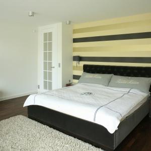 Wiodącym elementem aranżacji jest ściana za łóżkiem. Tapeta w pasy ułożone poziomo, powiększa wnętrze wizualnie. Projekt: Paweł Ejsmont. Fot. Bartosz Jarosz.