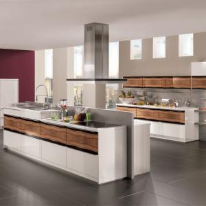 Fronty mebli kuchennych zdobi śnieżna biel oraz poziomy rysunek drewna, oprawiony w czarne ramy. Całość wykończono na wysoki połysk, co nadaje meblom fantazyjny wygląd. Fot. Nobilia, kuchnia Highlight.