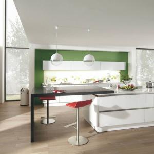 Modna kuchnia z dużą wyspą, znajdującą się w centrum pomieszczenia. Fronty mebli kuchennych wykończono na wysoki połysk, co idealnie współgra z minimalistyczną stylistyką. Fot. Wellmann, meble z programu G888 Vitus.