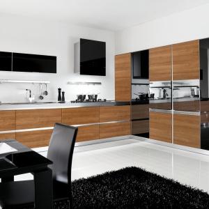 Drewniane fronty zestawiono z frontami z czarnego szkła. Całość prezentuje się stylowo i nowocześnie. Fot. Home Cucine, kuchnia Mela Noce Chiaro.