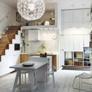 Oryginalna kuchnia, w której biała jest nie tylko zabudowa pod schodami, ale również niewielka wyspa, towarzyszący jej stół, a także... drewniana podłoga. Naturalny kolor drewna zdobi dolną zabudowę oraz stopnie schodowe. Fot. IKEA.
