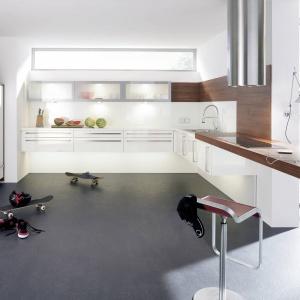 Białe fronty kuchenne zestawiono z blatem, ścianą oraz ramami okalającymi zabudowę w kolorze ciemnego, czekoladowego drewna. Fot. Alno, meble z programu 348 Alnocarme.
