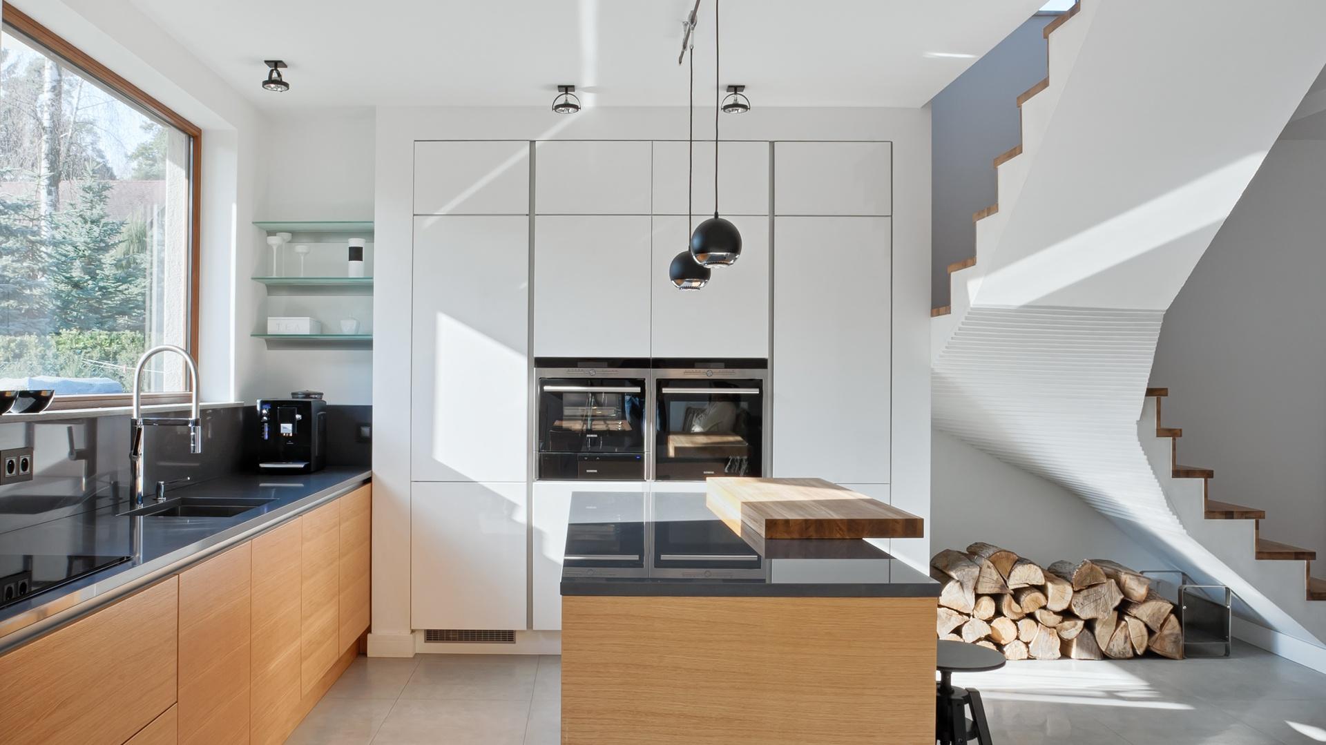Nowoczesna kuchnia z wysoką zabudową z białymi frontami w macie oraz dolna zabudową w kolorze drewna. Wszystko zamknięto w minimalistyczne formy. Fot. Atlas Kuchnie.
