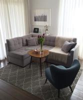 Centralny punkt pokoju zajmuje szara, narożna kanapa. Dzięki pikowaniom nie jest to nudny mebel. Podłogę zdobi prosty kilim, który doskonale sprawdza się u właścicieli czworonoga.