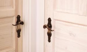 Klasyczne, bielone drzwi przyciągają wzrok. Stare mosiężne klamki zostały zakupione po wielu tygodniach poszukiwań na jednym z portali aukcyjnych.