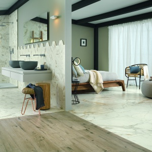 Podłoga w sypialni połączonej z łazienką może tworzyć spójną całość, bądź też, jeśli zastosujemy materiał o różnej fakturze, wizualnie zaznaczać odrębność obu pomieszczeń. Fot. Ragno.