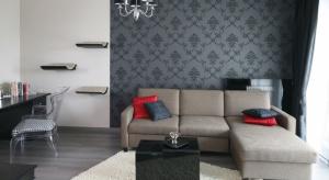 Nasz ekspert radzi, jak ozdobić ścianę nad sofą i komodą w salonie z aneksem.