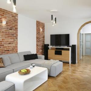W salonie przytulność buduje drewniany parkiet, ułożony w klasyczny wzór oraz czerwony odcień cegły. Projekt: inż. arch. Agata Piltz. Fot. Bartosz Jarosz.