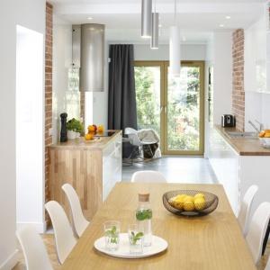 Kuchnia z jadalnią stanowią połączone ze sobą pomieszczenia. Masywny, drewniany stół doskonale koresponduje z białymi, lekkimi w formie krzesłami. Projekt: inż. arch. Agata Piltz. Fot. Bartosz Jarosz.