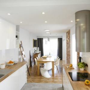 Brak górnej zabudowy na jednej ze ścian w kuchni dodał przestrzeni lekkości oraz pozwolił na montaż dekoracyjnego okapu. Projekt: inż. arch. Agata Piltz. Fot. Bartosz Jarosz.