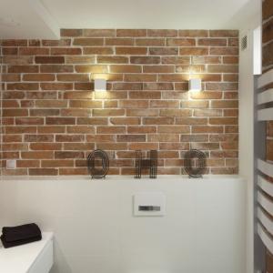 W łazience - podobnie, jak w kuchni - zestawiono ze sobą cegłę z białą zabudową i grzejnikiem. Projekt: inż. arch. Agata Piltz. Fot. Bartosz Jarosz.