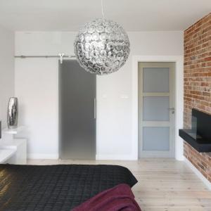 Ozdobny żyrandol nad łóżkiem harmonizuje z przezroczystym krzesełkiem, wprowadzając do wnętrza element stylistyki glamour. Projekt: inż. arch. Agata Piltz. Fot. Bartosz Jarosz.