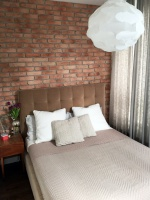 Przytulne, tapicerowane łóżko doskonale współgra z surową ścianą z czerwonej cegły.