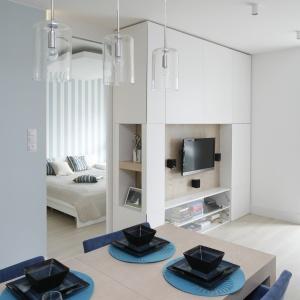 Siedząc przy stole można oglądać telewizję. Zabudowa RTV jest wykonana na zamówienie, z takich samych materiałów jak meble kuchenne.