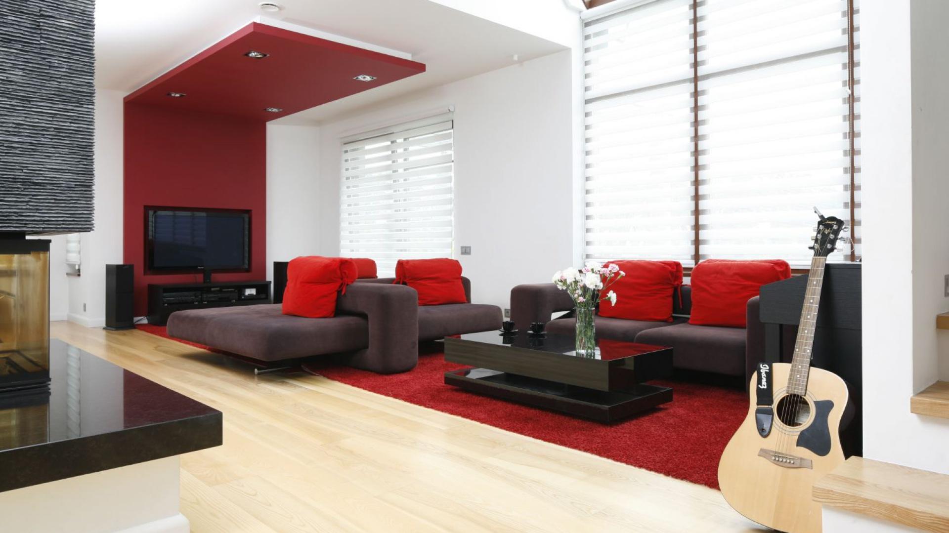 Salon ma wysokość dwóch pięter. Dominuje w nim czerń i biel, które ożywia czerwień. Zdobi ona nie tylko nowoczesne kanapy, ale też ściany i podłogi. Projekt: Michał Mikołajczak. Fot. Bartosz Jarosz.