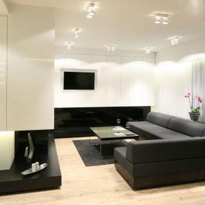 Elegancki salon urządzono w czarno-białej tonacji. Jego nowoczesny charakter podkreślają proste formy mebli. Projekt: Dominik Respondek. Fot. Bartosz Jarosz.
