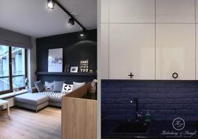 Błyszczące białe akrylowe fronty z kutymi czarnymi uchwytami to ulubiony element właścicielki mieszkania.