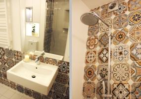 Łazienka z prysznicem urozmaicona została o płytki z kolorowym patchworkowym wzorem.