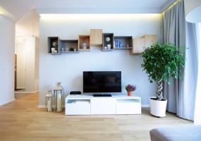 W nowoczesnym salonie urozmaicenia dodają nieregularnie zawieszone półki nad telewizorem.