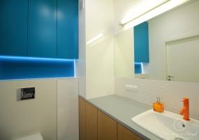 Turkusowe fronty meblowe i pomarańczowa bateria umywalkowa hipnotyzują od wejścia do łazienki.