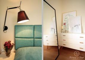 Wygodny turkusowy zagłówek nad łóżkiem to element charakterystyczny dla tej sypialni.